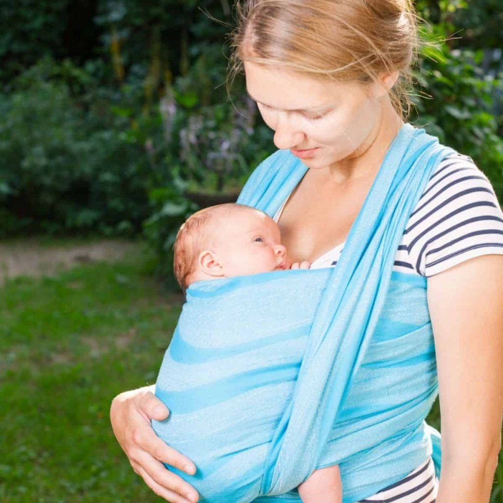 mother holding infant with a baby wearing wrap