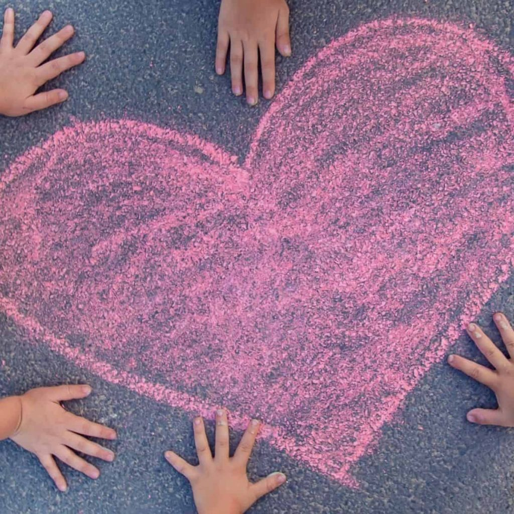 kids hands laid out on sidewalk next to a pink heart-shaped chalk outline