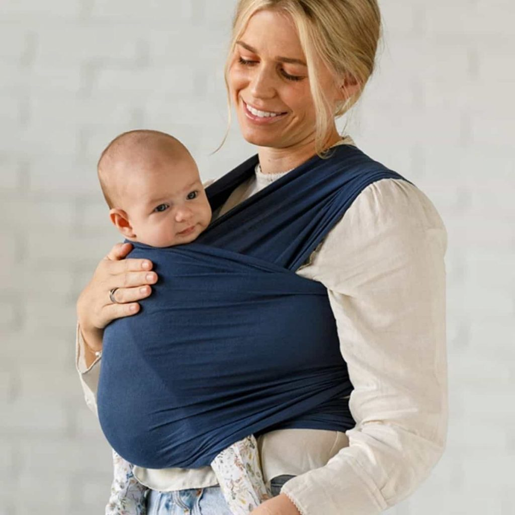 Mom comfortably wears baby in a blue solly wrap