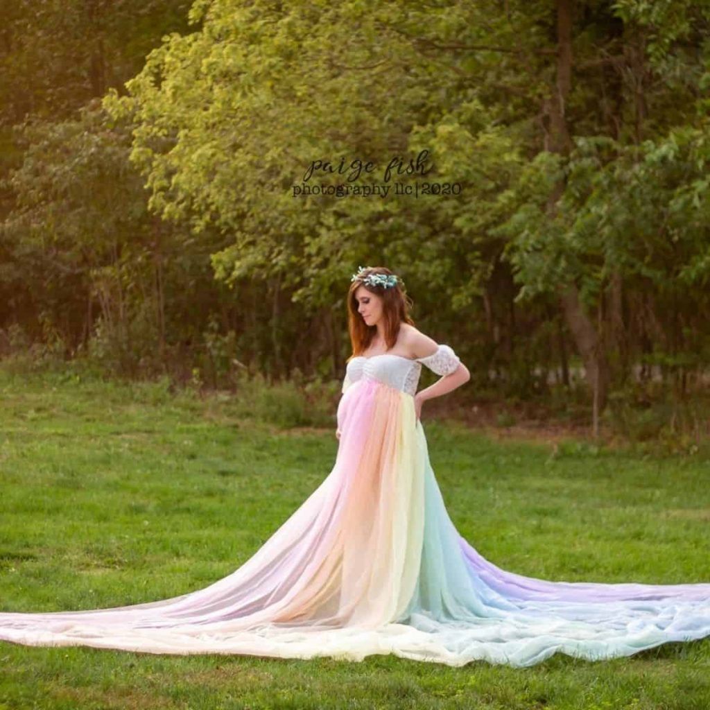 pregnant woman is wearing pastel rainbow tossing skirt in a field