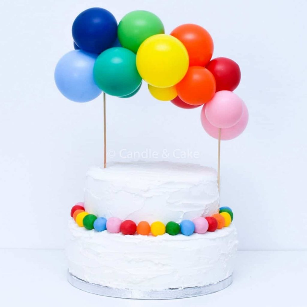rainbow balloon garland cake topper on top of two-tiered cake with white icing