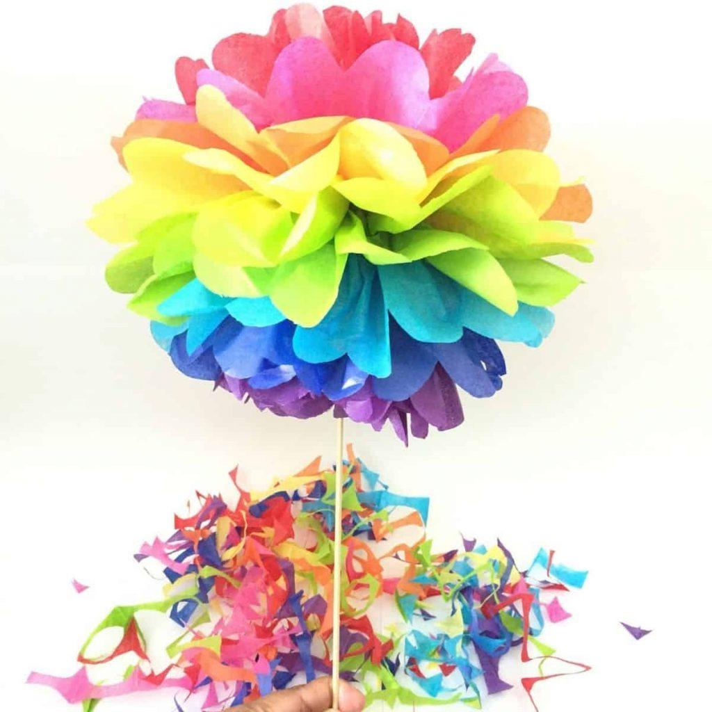 hand holding up a rainbow tissue paper pom pom