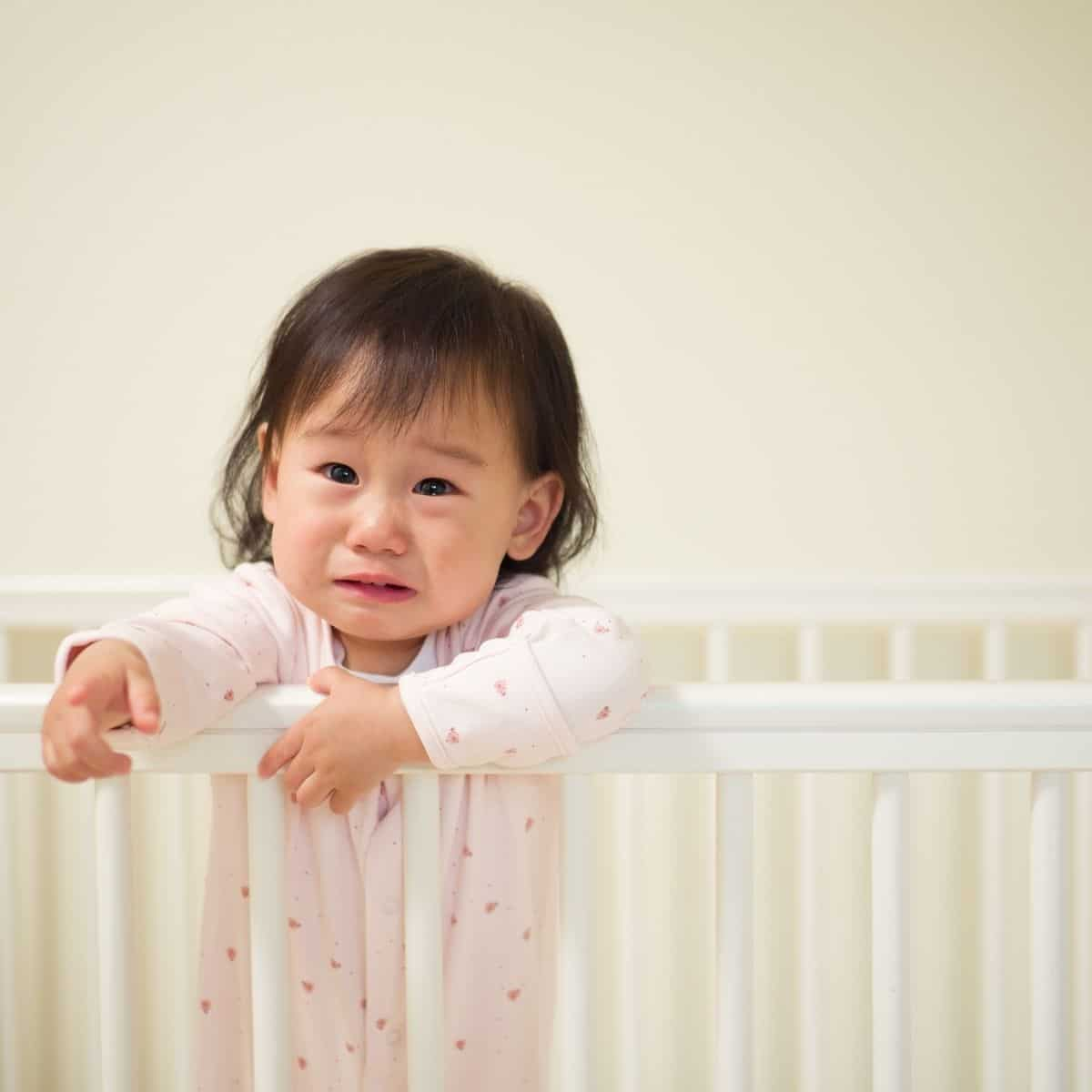 baby girl is crying while standing in her crib