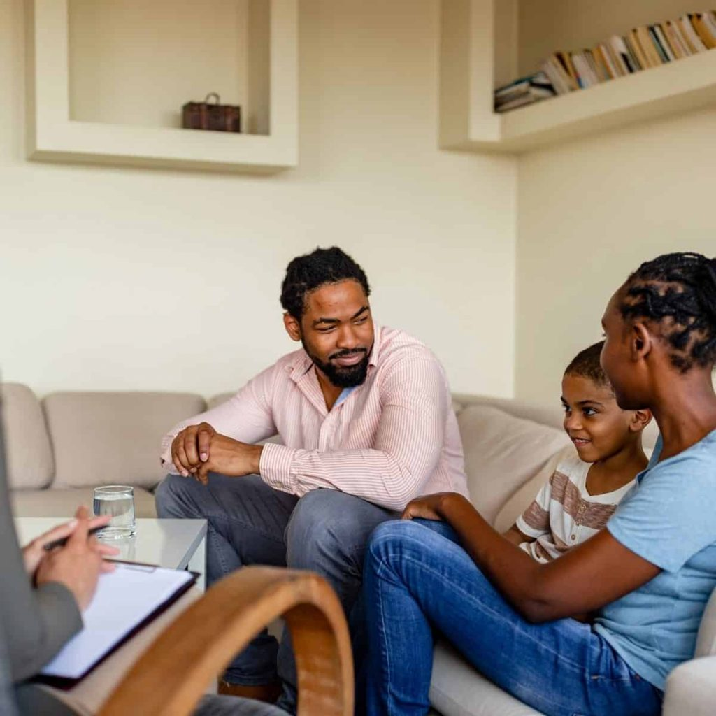 father smiles at son and wife during a session with a therapist