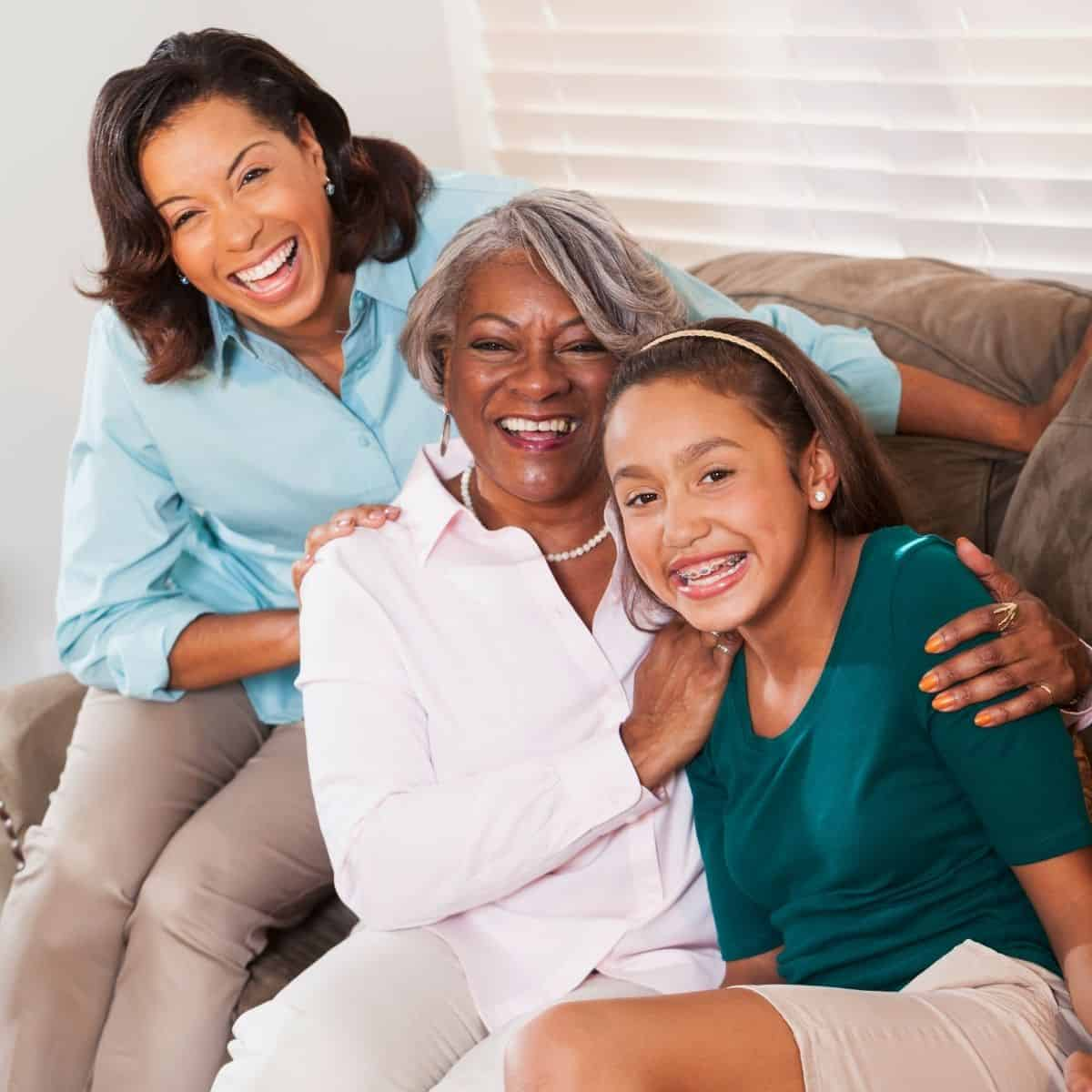 granddaughter, grandmother, and mother pose for a photo while sitting on a couch