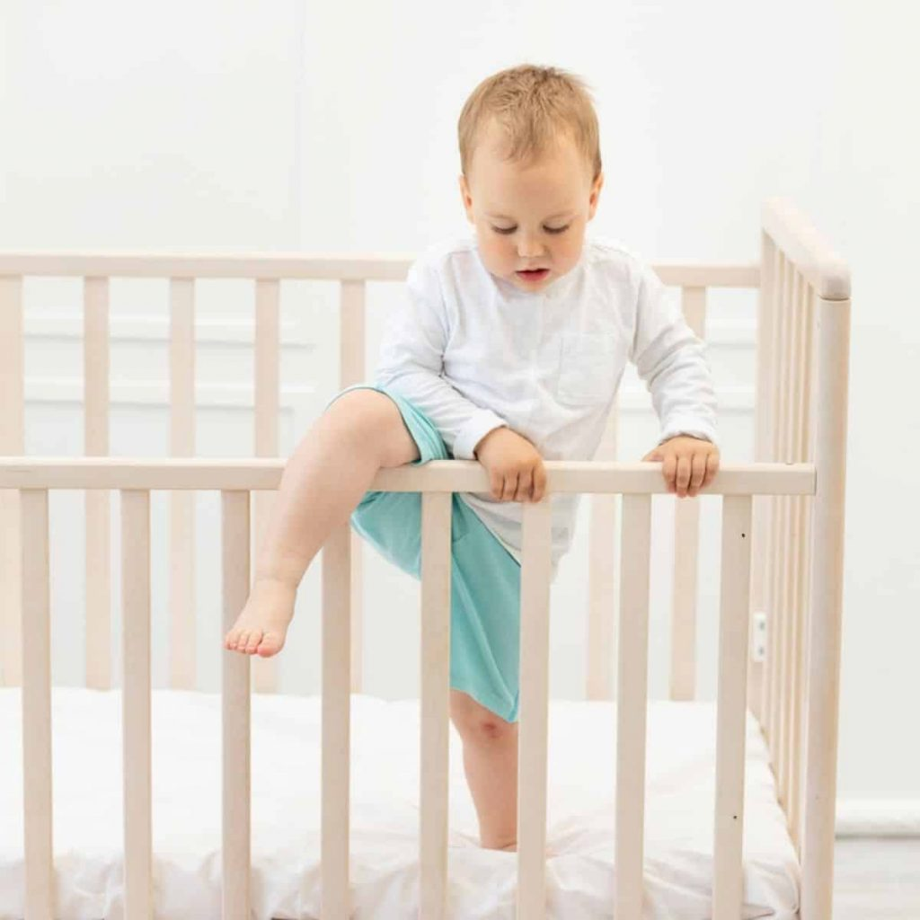 toddler attempting to climb out of his crib