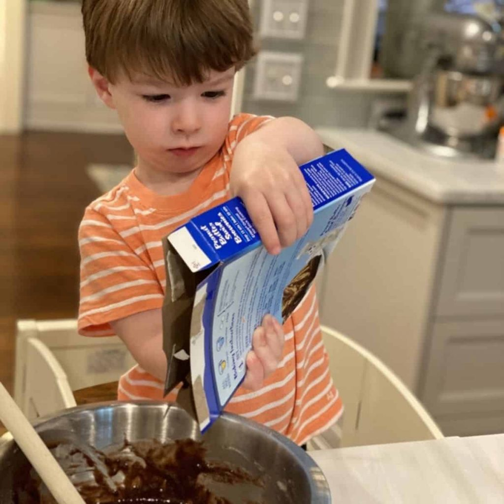 toddler pours brownie mix into mixing bowl