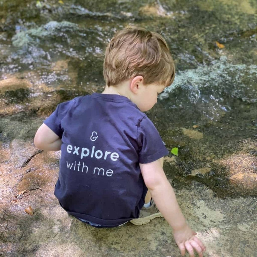 toddler plays by a riverbank