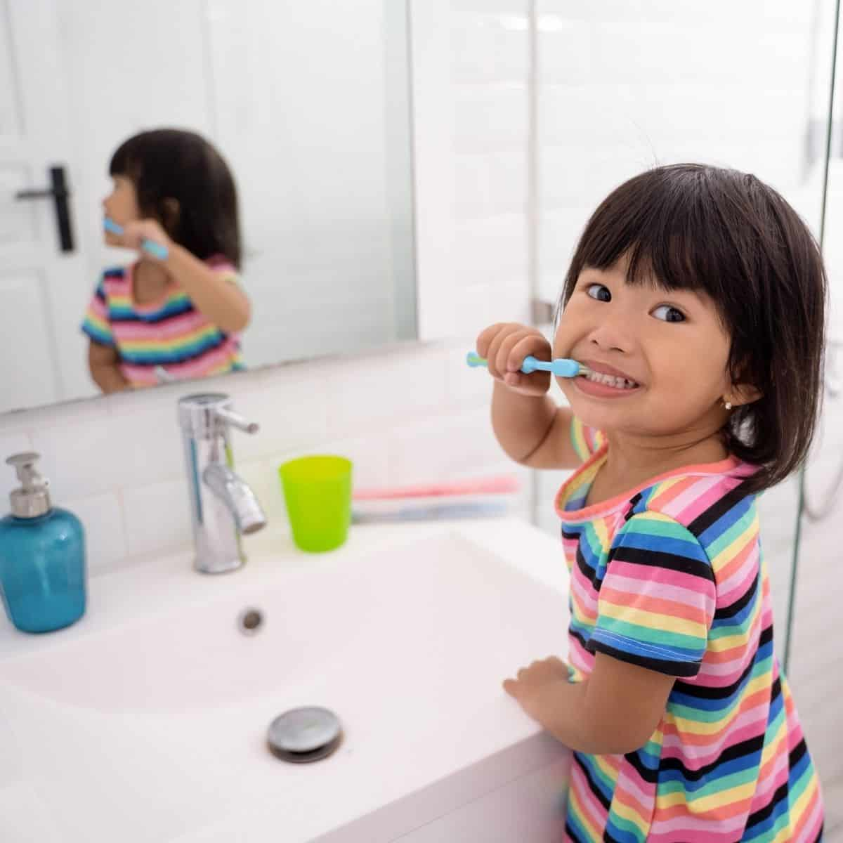 young toddler brushes her teeth in front of bathroom sink with her reflection in mirror