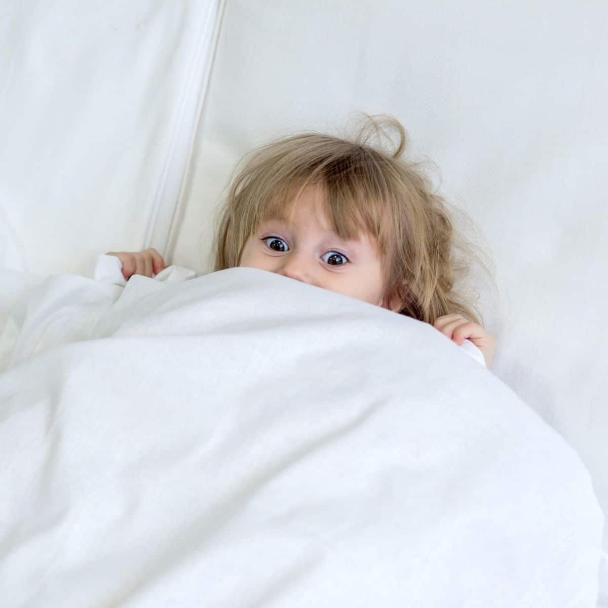 little girl hiding underneath white bedsheets with her eyes and hands showing