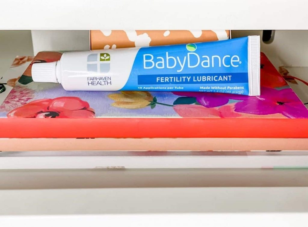 Tube of baby dance fertility lubricant by fairhaven health lying on top of books on a nightstand