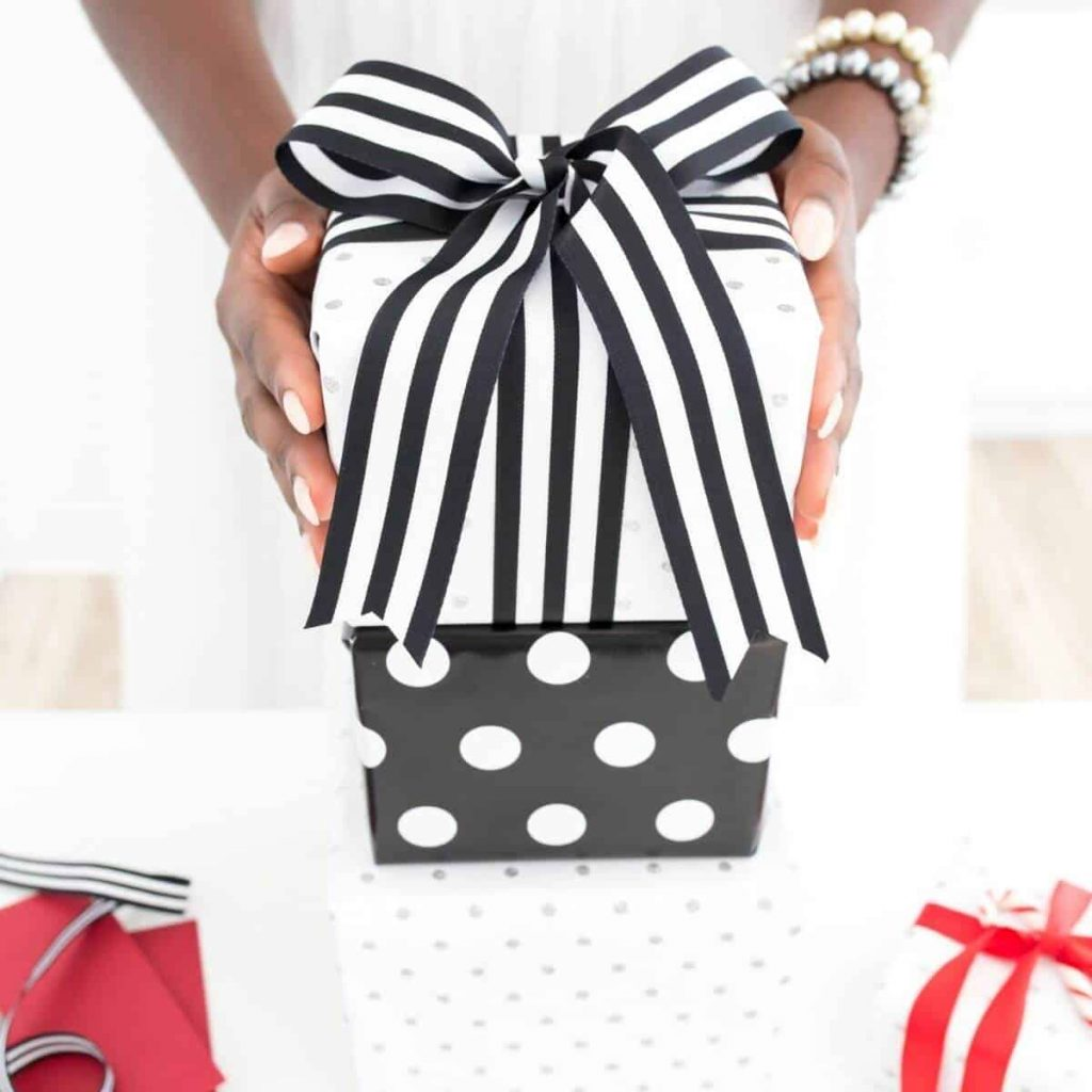 Three gifts are stacked in the middle of the photograph, and a woman's hands hold the top gift. She is wearing pearl bracelets.