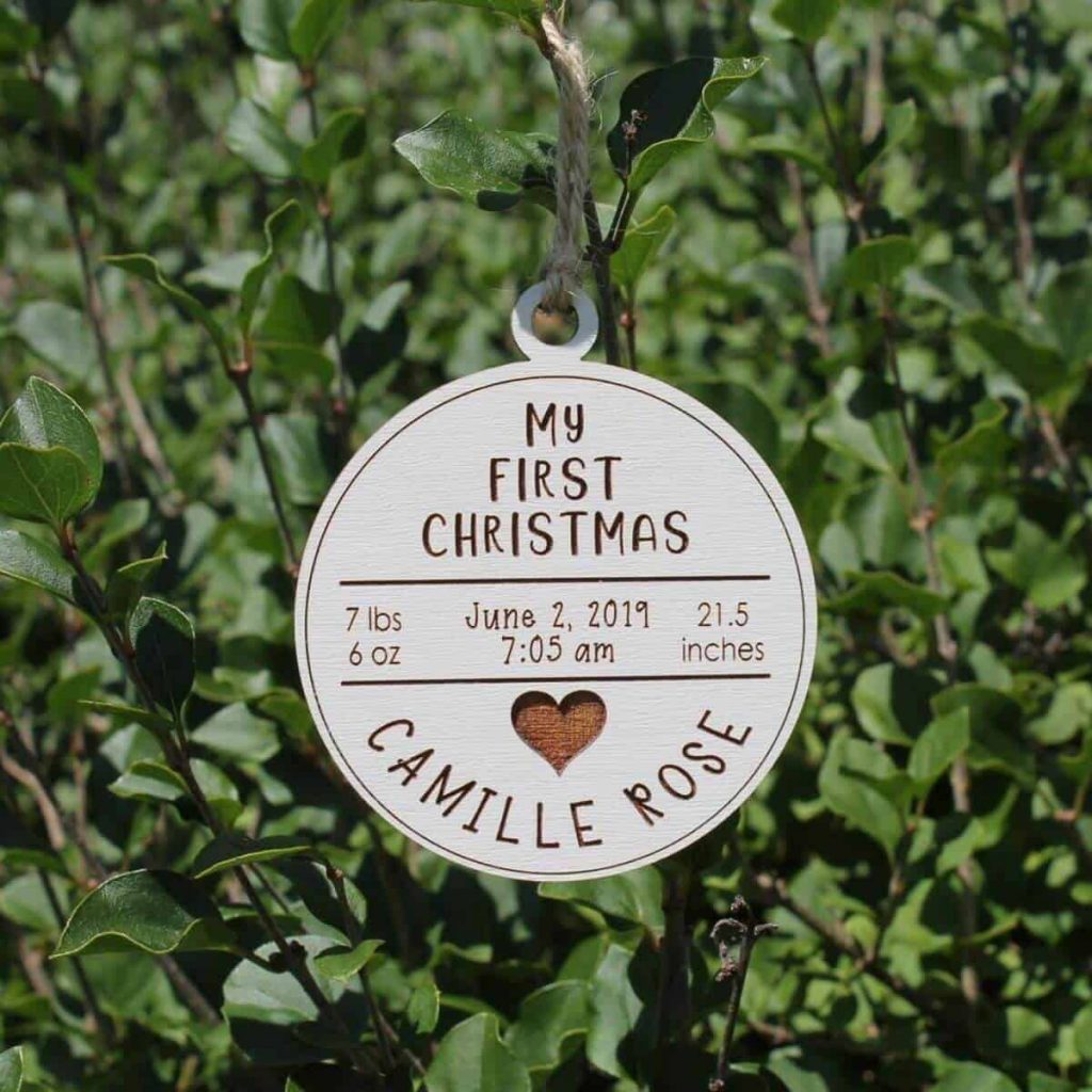 cream colored wooden ornament hanging on a Christmas tree that says my first Christmas with baby's name, birthdate, and height and weight at birth