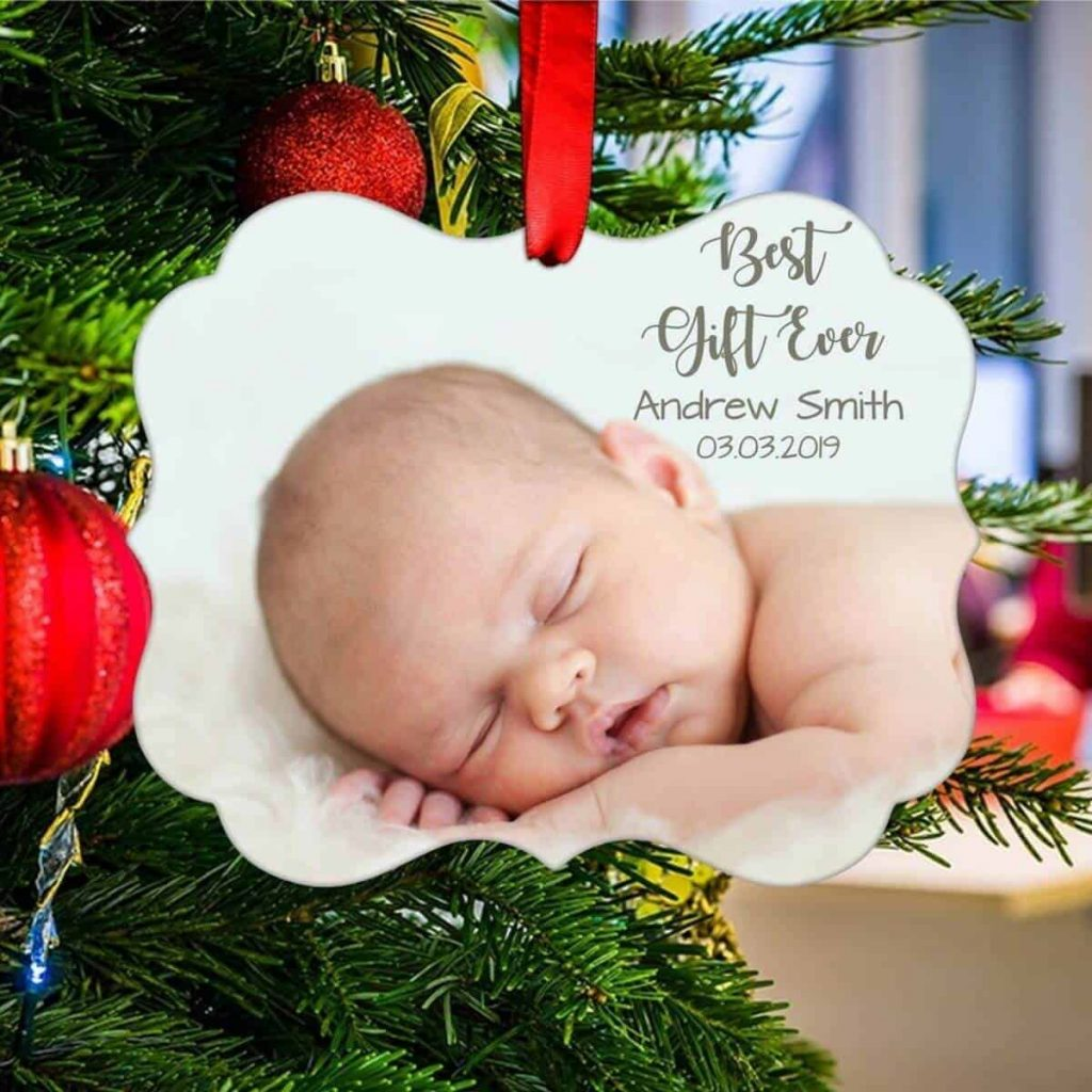 a ceramic Christmas ornament hanging on a tree with a precious photo of a newborn baby with his name and birthdate