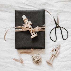 This image shows a black present tied up with a nutcracker and bow.