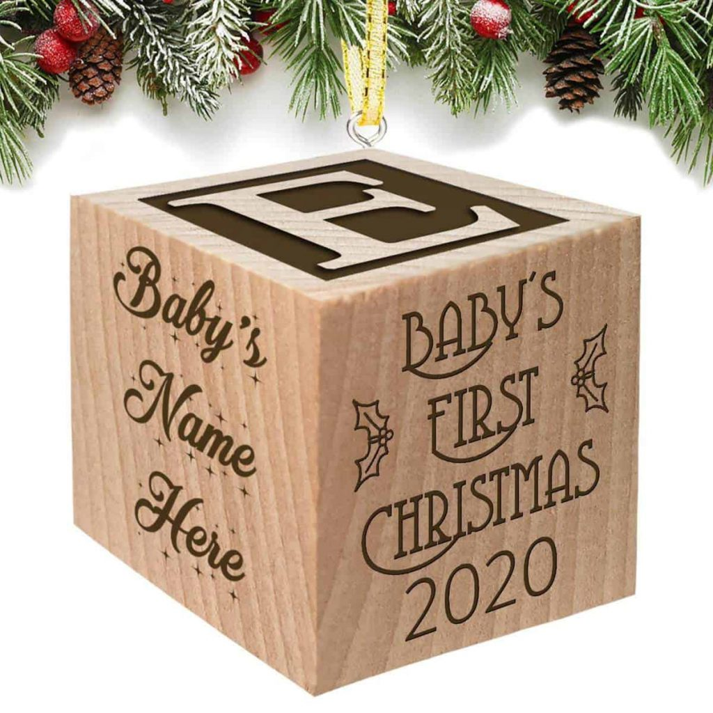 3D wooden block Christmas ornament with a letter on one side, baby's name on another, and baby's first christmas on another