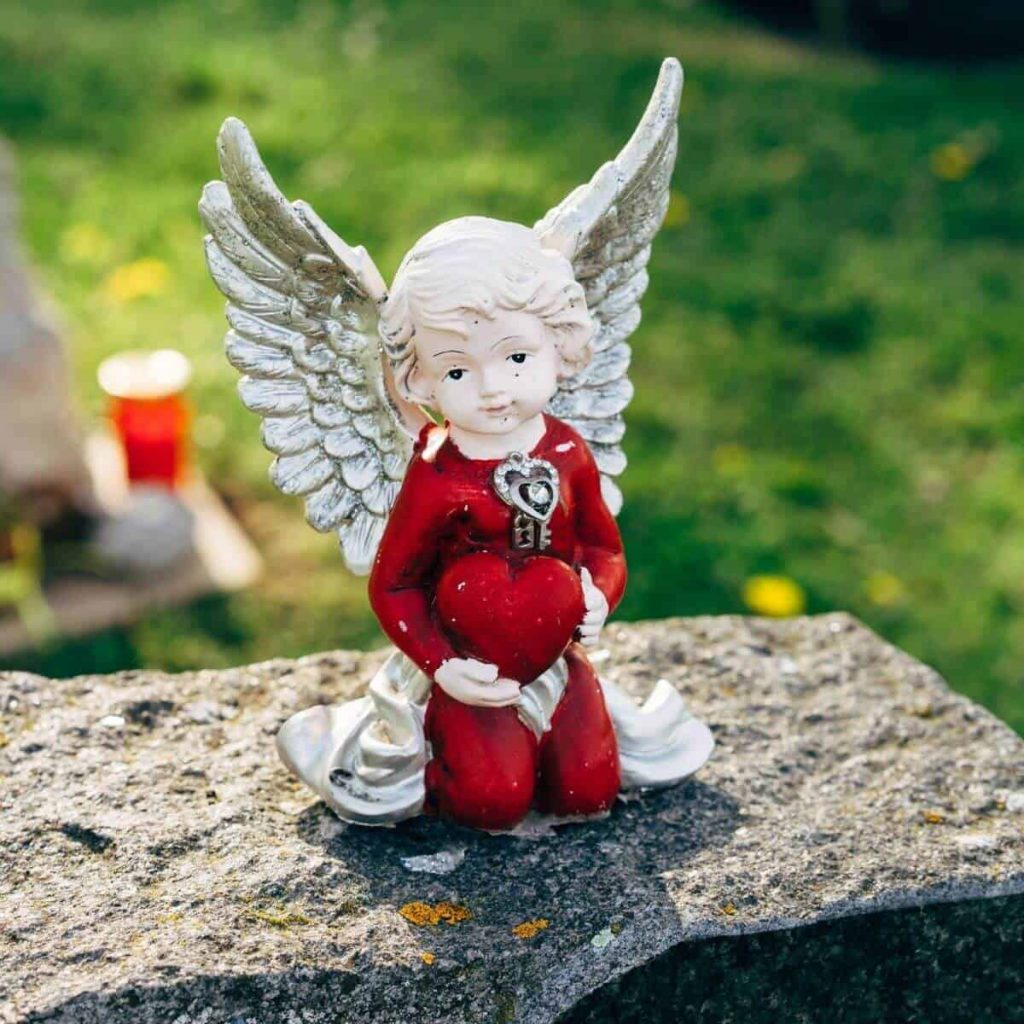 A small decorative angel statue sits atop a gravestone.