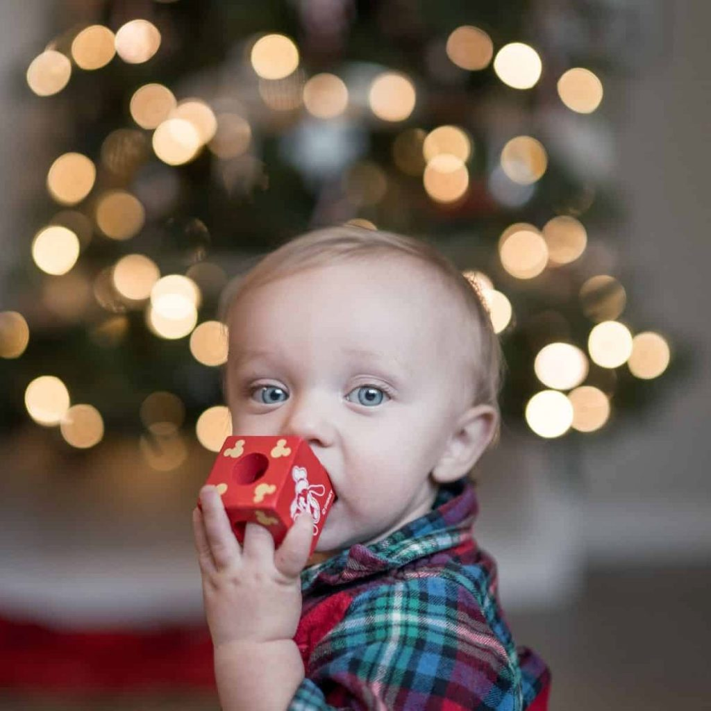 A baby with bright blue eyes chews on a Christmas ornament in front of a blurred Christmas tree with lights.