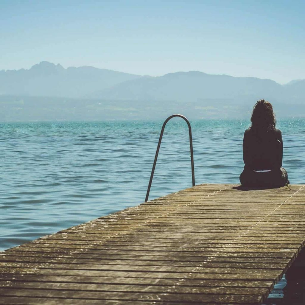 This photo shows a woman sitting alone at the end of a pier. It is used to convey loneliness and sadness.