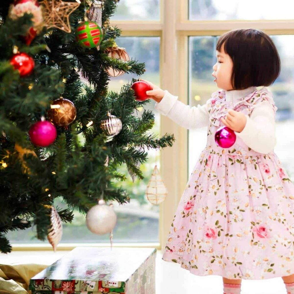 A toddler in a pink dress decorates a Christmas tree.