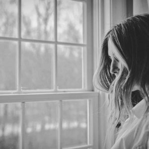 This black and white image shows a woman grieving by a window.