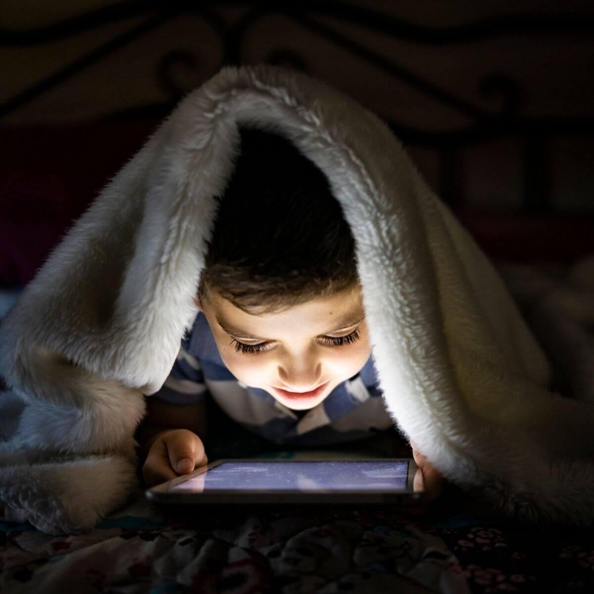 Little boy watches screen under cover header