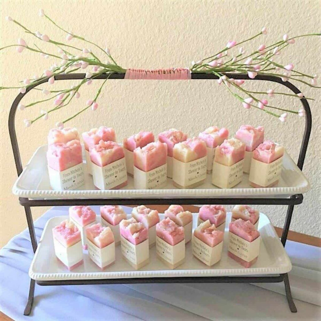two tiers of trays with soft pink flowers tied to top and small pink personalized hand soaps on each tray