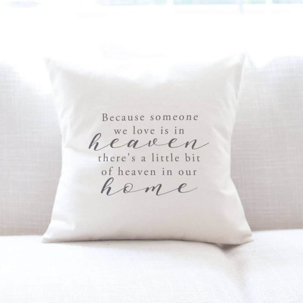 White pillow on white couch with soft lettering that says because someone we love is in heaven, there's a little bit of heaven in our home