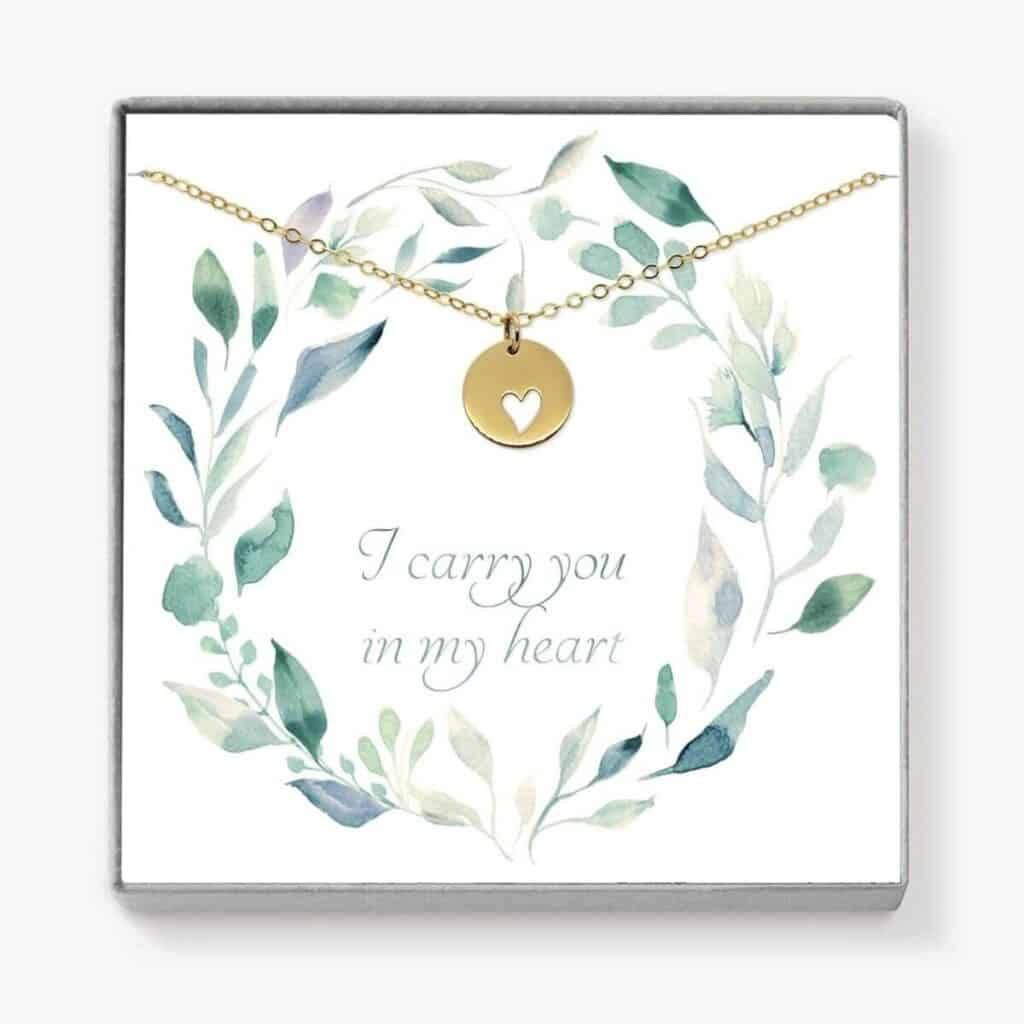 Gold circular pendant necklace with small heart cutout with a note on the box that says I carry you in my heart