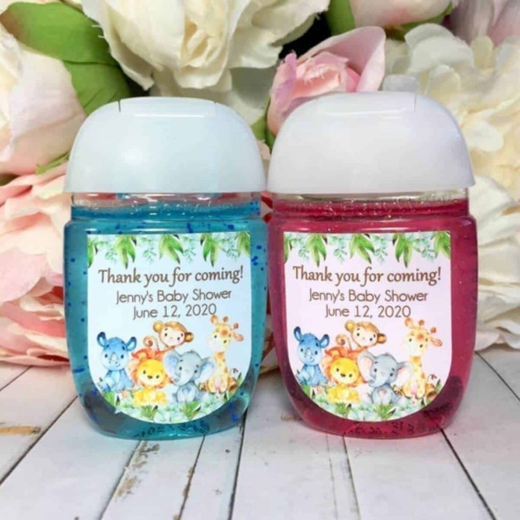 two small bottles of hand sanitizer, one pink and one blue, sitting in front of flowers, with a sticker on each bottle that says thank you for coming to jenny's baby shower