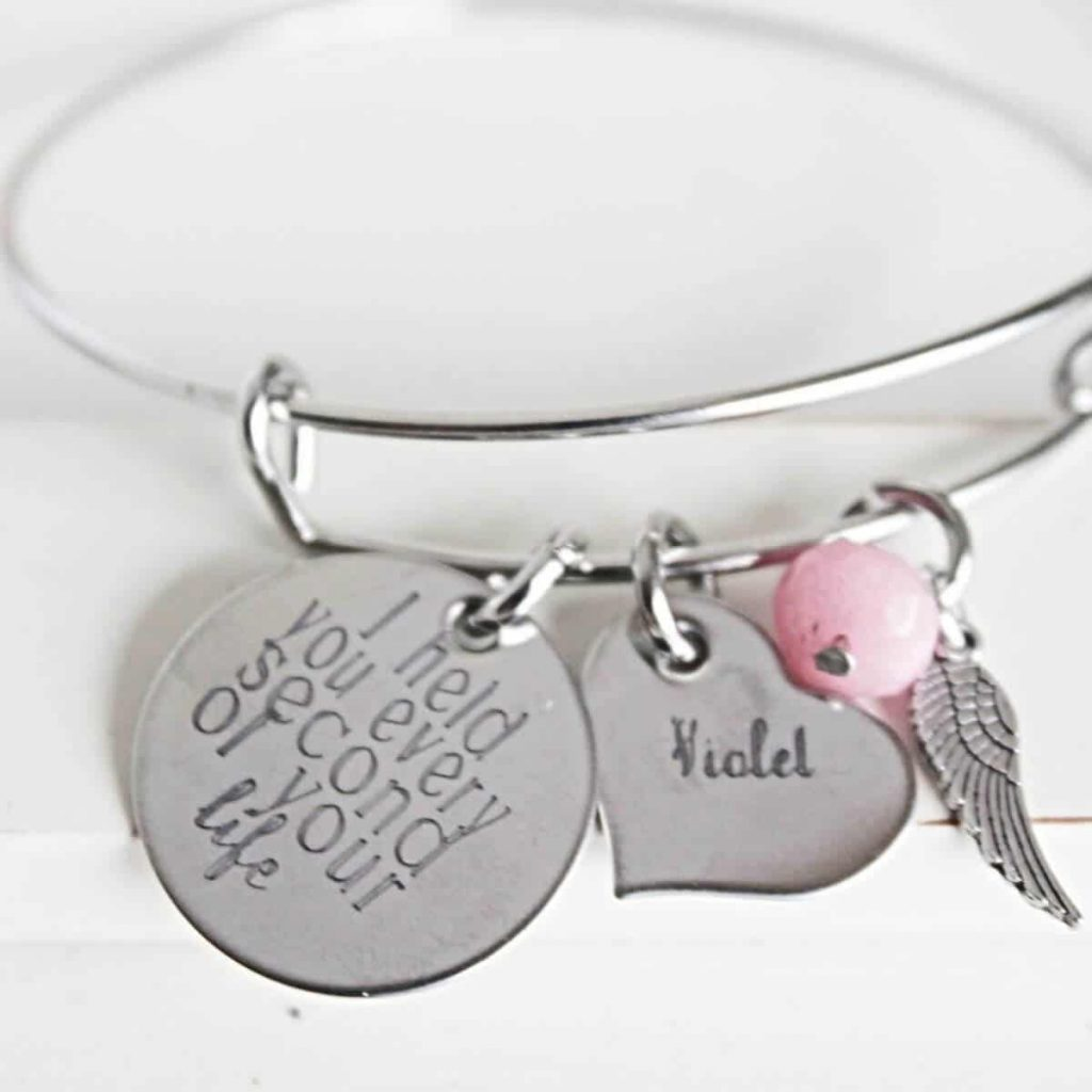 silver charm bracelet with a heart-shaped charm with the name violet, an angel wing charm, and a round charm that says I held you every second of your life