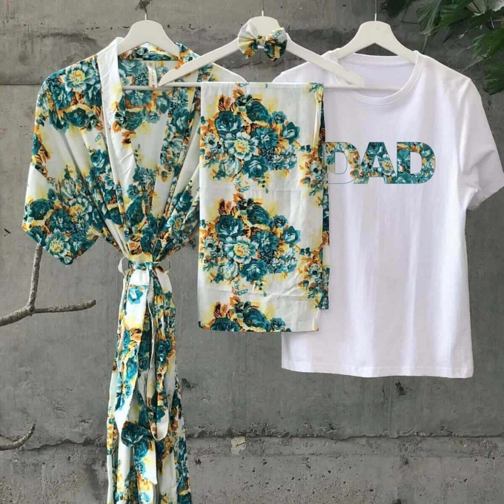 a long cream robe with green and yellow floral print hangs on a coat hanger next to a swaddle blanket with the same pattern and a t-shirt that says dad