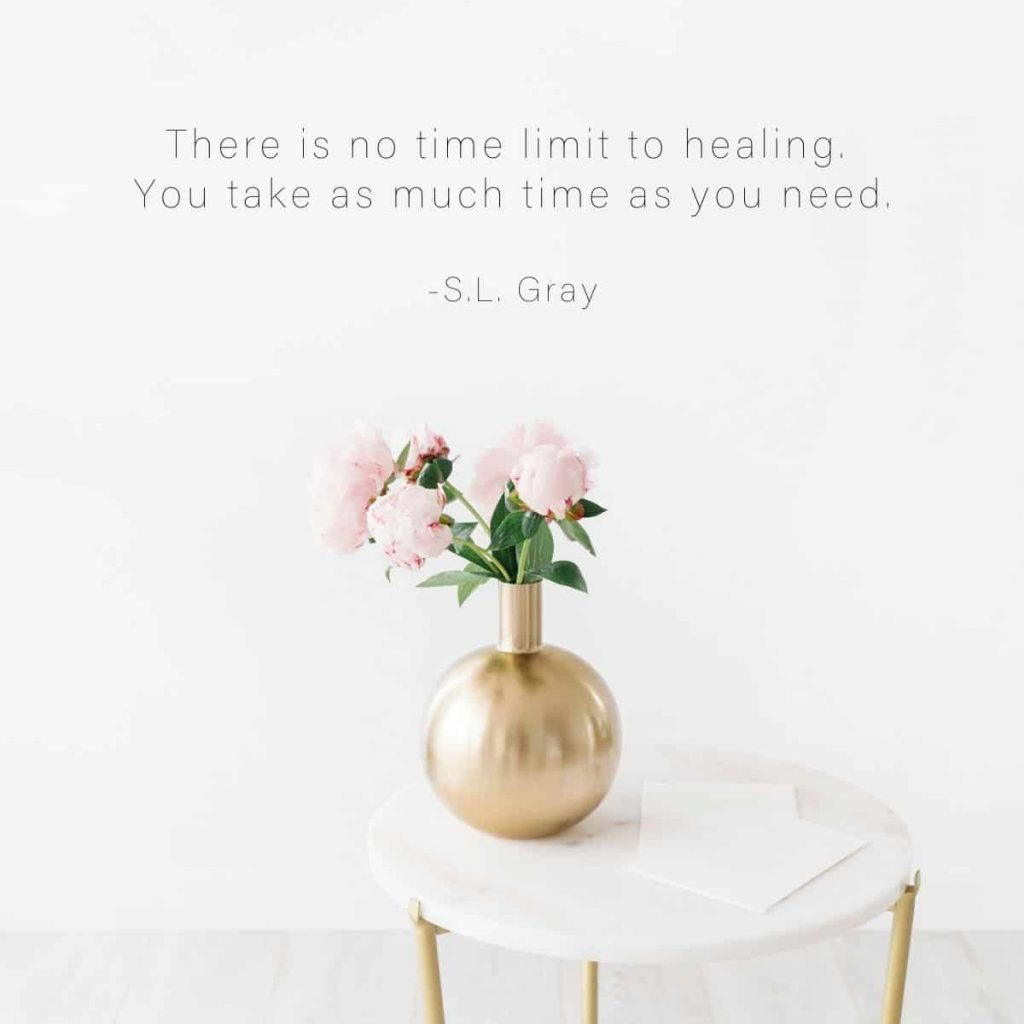 Soft flowers sitting in gold vase on a table with text above that says There is no time limit to healing.  You take as much time as you need by S.L. Gray